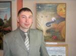 """Андрій Биков поряд із своїм """"Де той, котрий?"""", де простежується схожість автора із усміхненим сонечком"""